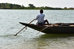 Indian village fishing boat with a man called nouka located at Sahupara village  Odisha in Brahmani river