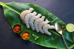 Indian White cleaned prawns, shrimps, on green banana leaf with Spices and cooking ingredients on black background. preparation for the prawns fry or shrimp curry. copy space.