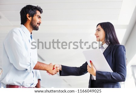 Indian woman and man wearing formals shaking hands  #1166049025