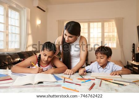 Indian woman checking how her children doing homework