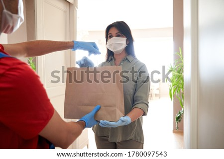 Indian woman customer wearing face mask and gloves taking delivery paper eco bag from man courier holding grocery food package delivering supermarket takeaway order standing at home. Safe delivery.