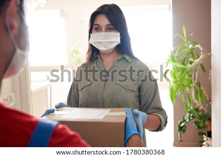 Indian woman customer wears medical face mask gloves holds courier delivery box stands at home. Deliveryman or postman gives parcel package delivering post mail shipping order to indian female client.