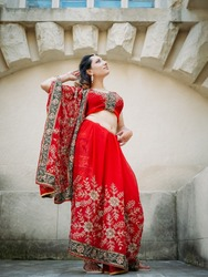 Indian woman dance on streets of ancient architecture city of India dressed in red Sari, decorated with traditional ornaments and Mehendi patterns henna drawings on hands.