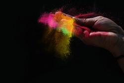 Indian woman hand colourful holi powder splash at black background, Holi celebration