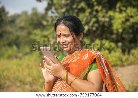Indian woman in traditional cloth using smartphone at outdoor. Changing human life concept.