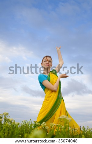 Indian Woman in traditional Sari  / blue sky and green grass