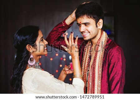 Indian woman is giving blessings to the man by putting tika on his forehead while wearing traditional ethnic clothes