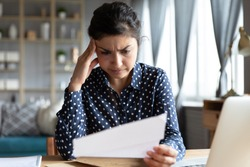 Indian woman sit at desk hold document read paper letter feels disappointed shocked by bad news. Financial trouble bank debt notice, medical test results health problems, huge domestic bills concept