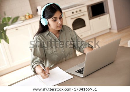 Indian woman student wear headphones learning online watching online class webinar seminar training looking at laptop computer elearning remote lesson writing notes, video conference calling at home.