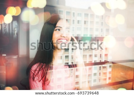indian woman talking on phone through the window