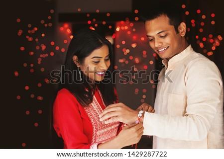 Indian woman tying rakhi on her brother's hand to celebrate Raksha Bandhan (Rakshabandhan) / Bhai dooj