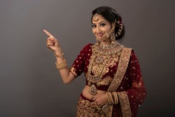 Indian woman with happy expressions and wearing the bridal wear and bridal jewelry