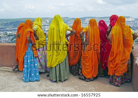Indian women in brightly colored saris on the roof of a Rajput palace. Tiger Fort, Jaipur, Rajasthan, India