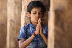 Indian young boy meditating at hindu temple