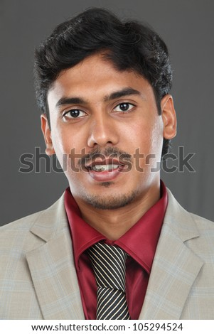Indian young businessman posing to the camera on white background.