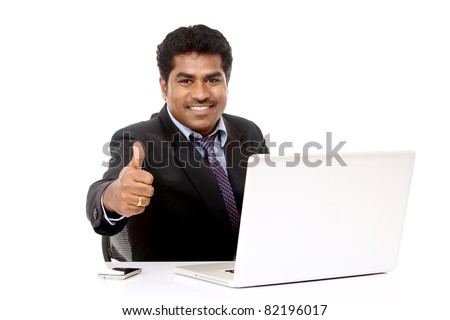 Indian young businessman working in laptop isolated on white. - stock photo