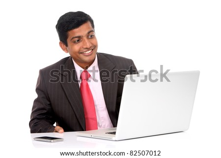 Indian young businessman working in laptop isolated on white.