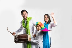 Indian young couple with kid celebrating holi festival. Dancing and playing drums and holding plate full of colours