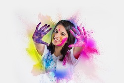 indian young girl showing colourful palm and celebrating holi with colour splash