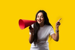 Indian young girl with megaphone made out of paper. Announcing, screeming or advertising while standing against yellow studio background