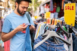 Indian young man looking and buying clothing from outdoor street market of Delhi, India at day time.