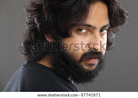 Indian young man with long hair on grey background. - stock photo