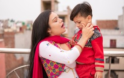 Indian young mother scolding her little son and pulling his cheeks. She is standing near railing and spending leisure time with her son. She is wearing traditional dress salwar Kameez and Dupatta.
