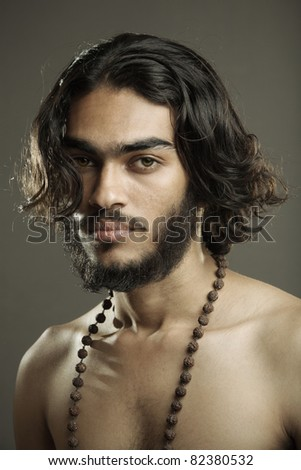 Indian young sadhu posing to the camera. - stock photo