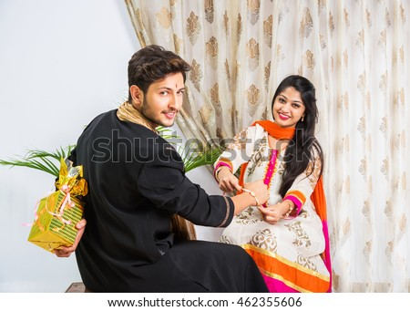 Indian young sister tying rakhi on brother\'s wrist, a tradition on Raksha Bandhan festival