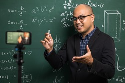 Indian young teacher man teaching online video conference live stream by smartphone. Asian teacher teaching mathematics class webinar online for students learning.