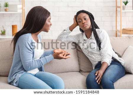 Indifference in friendship. Bored black girl tired of listening her talkative girlfriend while sitting on sofa at home together