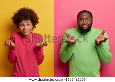 Indifferent ethnic teenagers shrug shoulders and stand hesitant, make decision, choose between something, have doubts, wear bright pink and green jumpers, stand indoor. Colorful vivid background