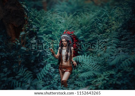 Indigenous American Indian walks in thickets of dark jungles. Princess Pocahontas. Girl in a leather suit of ethnic hunters. Artistic Photography. #1152643265