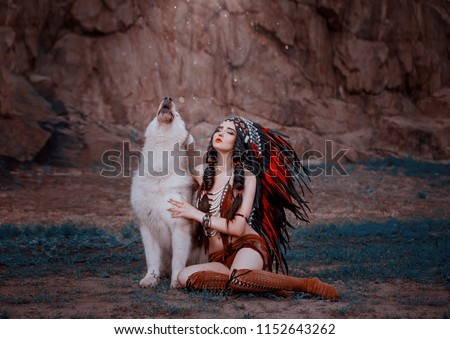 Indigenous American Indian wings with a wolf, a battle cry. The background of the rock. A wild woman celebrates the victory. A luxurious roach with very long feathers. Hairstyle - two braids