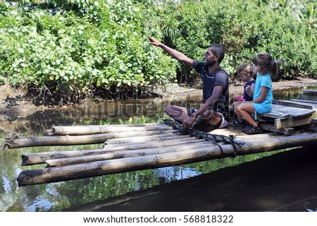 Indigenous Fijian man and two tourist children ride on a traditional Fijian bamboo boat over a water stream in Vanua Levu island, Fiji. #568818322