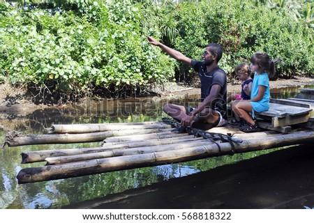 Indigenous Fijian man and two tourist children ride on a traditional Fijian bamboo boat over a water stream in Vanua Levu island, Fiji. #568818322