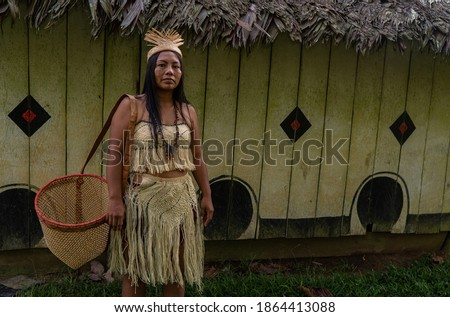 Indigenous woman from the Huitoto tribe of the Colombian Amazon in front of a maloka with a traditional basket