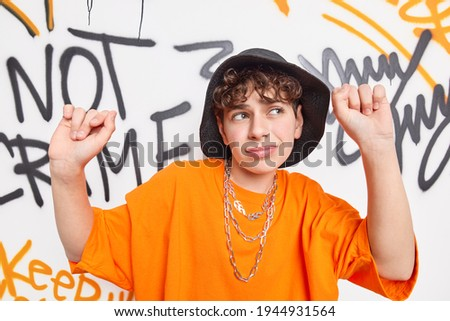 Indigenous young people and street art concept. Teenager dances to rap music against artwork wall wears black hat and orange t shirt spends free time in public place belongs to gang culture. Stock photo ©