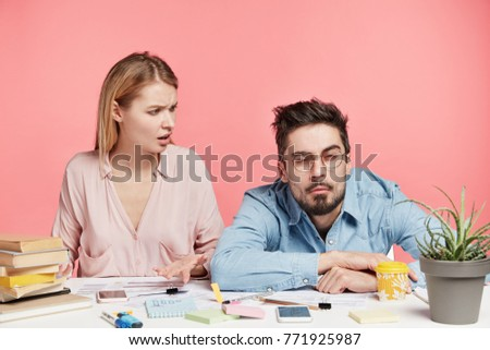 Indignant female student looks at her male groupmate who has sleepy expression in bewilderment, says that they have much work and no time for relaxation, asks to collect his strength to finish report #771925987