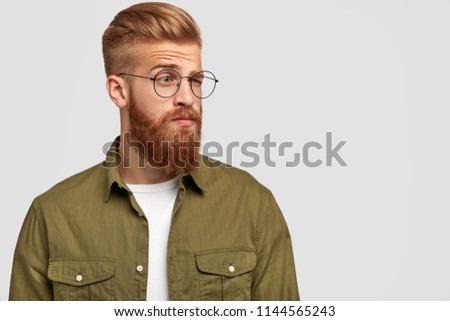 Indignant ginger male looks aside with puzzled thoughtful expression, raises eyebrows, wears glasses, wears fashionable clothing, stands against white background with copy space for your promotion #1144565243