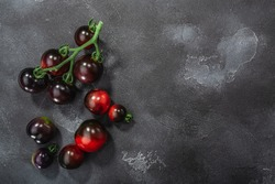 Indigo Rose heirloom cherry tomatoes on the vine atop washed dark concrete backdrop, top view