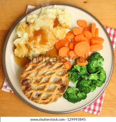 Individual chicken pie with mash, vegetables and gravy.