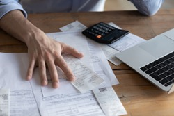 Individual entrepreneur make analysis of firm expenses, accountant do paperwork concept. On desk lot of receipts, calculator and laptop close up view. Man sit at table reviewing bills, managing budget