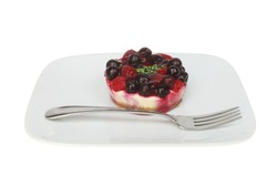 Individual mixed berry cheesecake with a fork on a plate isolated against white