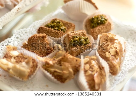 """Individual portions of baklava laid in a white paper tray displayed for clients. Traditional arabic pastry, eaten to break the fast in Ramadan or other festive days like """"Eid el-Iftar""""."""