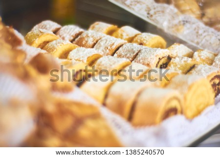 Individual portions of sliced roll spiral cake. Chocolate layered dough swirl shape. Covered with glass sugar. Bakery shop vitrine display.