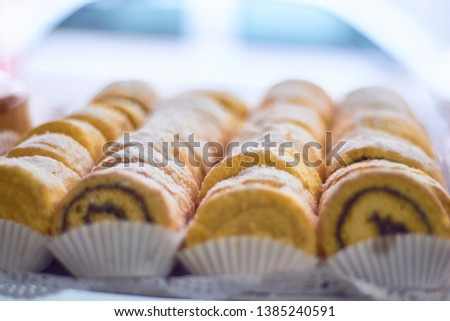 Individual portions of sliced roll spiral cake. Chocolate layered dough swirl shape. Covered with glass sugar. Bakery shop display.