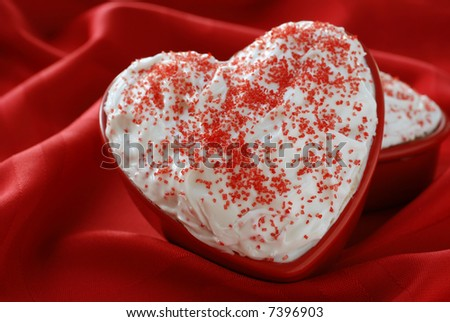 Individual sized, heart-shaped cakes with white frosting nestled in the soft folds of a red tablecloth.  Shallow dof.