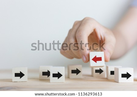 Individuality and leadership concept,women hand picked wooden block with red arrow facing the opposite direction black arrows, Unique, think different, individual and standing out.