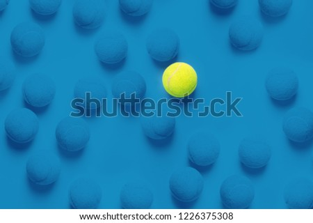 Individuality concept with tennis balls top view duotone blue background and one different ball